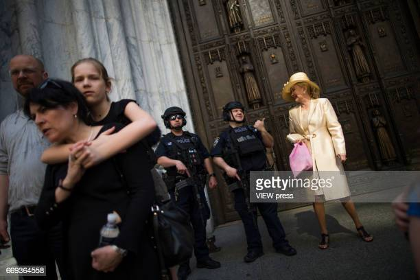 NYPD officers stand guard at one of the entrance of San Patrick Cathedral while people take part in the Annual Easter parade on April 16 2017 in New...