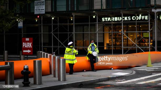 NYPD officers stand guard next to flood barriers used to prevent flooding at the South Street Seaport as the city gets ready for tropical storm...