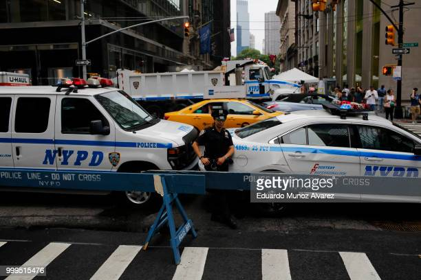 NYPD officers stand guard on streets as fans arrive to watch the World Cup final match between France and Croatia on July 15 2018 in New York City...