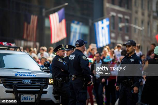 NYPD officers stand guard while people take part in the Annual Easter parade on April 16 2017 in New York City The Easter Parade and Easter Bonnet...