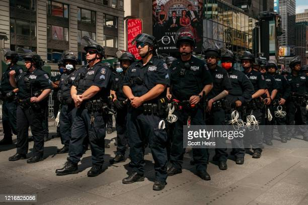 Officers stand in formation as nearby demonstrators hold a rally in Times Square denouncing racism in law enforcement and the May 25 killing of...
