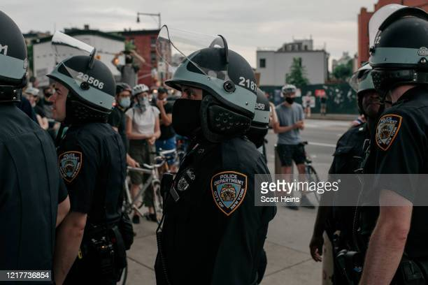 Officers stand in line near a demonstration denouncing systemic racism in law enforcement in the borough of Brooklyn minutes before a citywide curfew...
