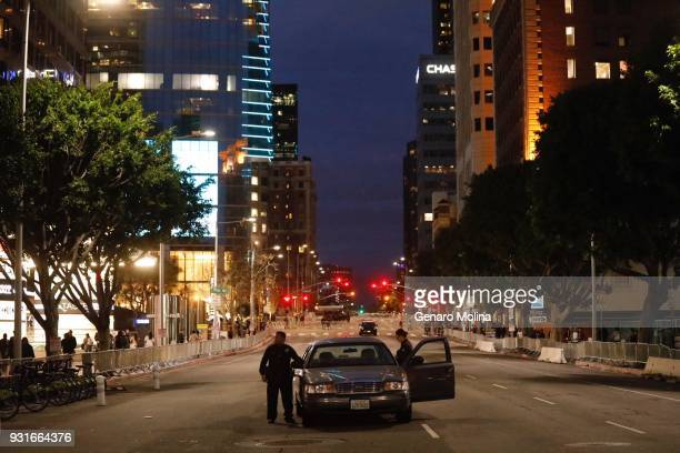 LAPD officers stand in the middle of a closed Figueroa Street waiting for the arrival of President Trump who will be staying at the Intercontinental...