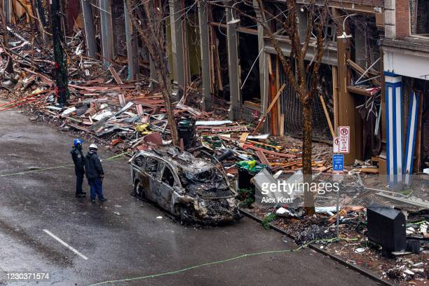Officers stand next to an invcinerated vehicle and observe damage down to the historic buildings on Second Avenue on Decemeber 31, 2020 in Nashville,...