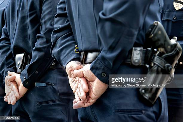 officers standing with hands behind - forze di polizia foto e immagini stock