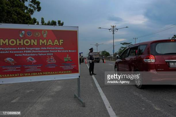Officers stop vehicles on the highway during largescale social restrictions to curb the spread of coronavirus in Pekanbaru Riau Province Indonesia...