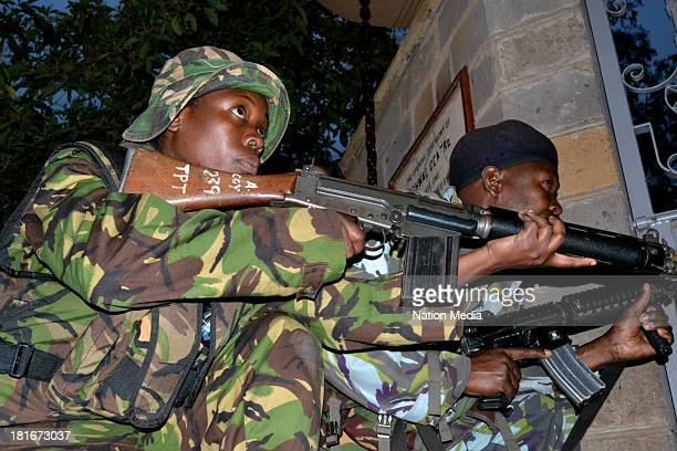 Officers take cover at Westgate Mall during a shoot-out with the terrorists on September 23, 2013 in Nairobi, Kenya. The attack occurred on Saturday,...