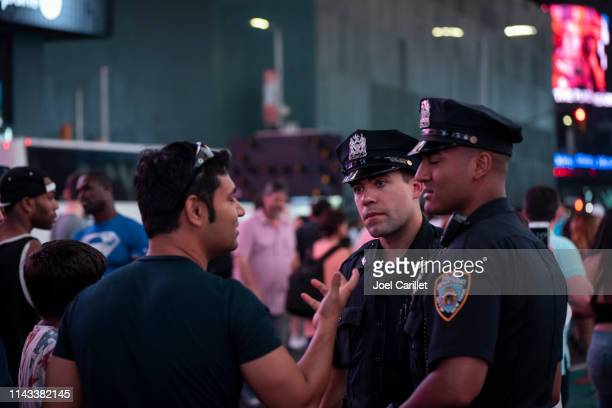 nypd officers talking with visitors in times square - new york city police department stock pictures, royalty-free photos & images