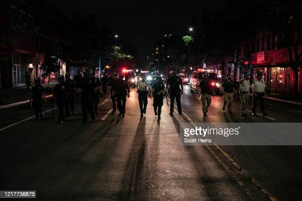 NYPD officers trail a peaceful protest march denouncing systemic racism in law enforcement that violated a citywide curfew on June 4 2020 in New York...