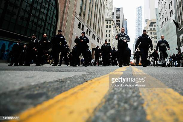 NYPD officers try to clean the street while people take part in a protest against Republican presidential candidate Donald Trump on March 19 2016 in...