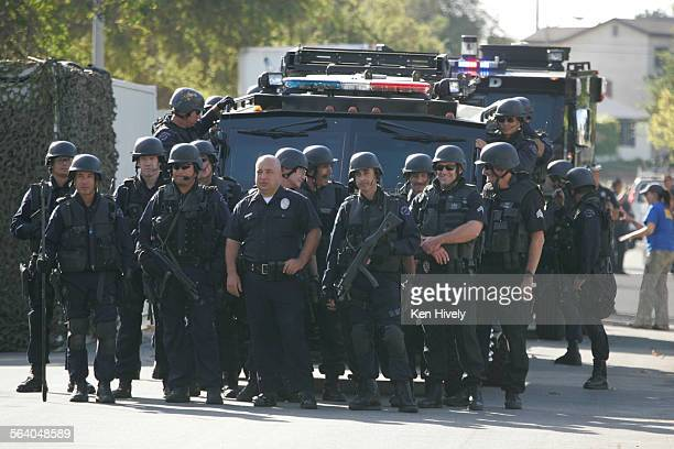 Officers wait with equipment for the demolition of a house for Extreme Makeover: Home Edition during live taping on Demolition Day in Redondo Beach,...