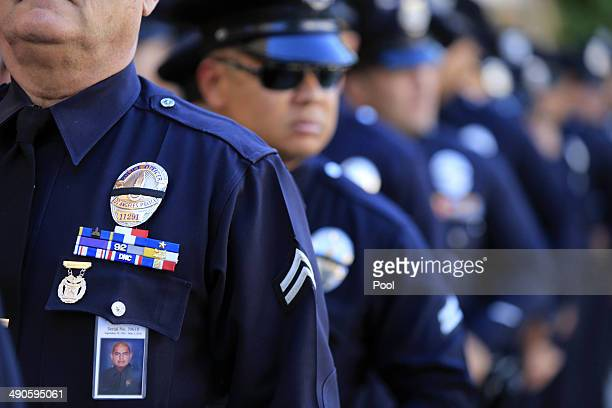 Officers wear a badge honoring fallen officer Roberto Sanchez during a memorial service at the Cathedral of Our Lady Of Angels May 14, 2014 in Los...
