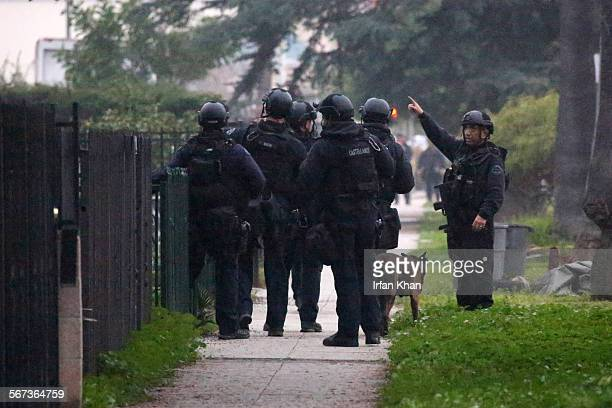 Officers with a K-9 dog search the Chesterfield Square neighborhood of South Los Angeles for suspects after an officer-involved shooting early...