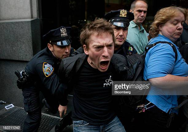Officers with the New York City Police Department arrest a protester during an Occupy Wall Street demonstration in New York, U.S., on Monday, Sept....