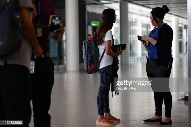 A official checks the passport of a passenger recently arrived from Mumbai in India in Terminal 2 at Heathrow Airport in London on July 16 part of...