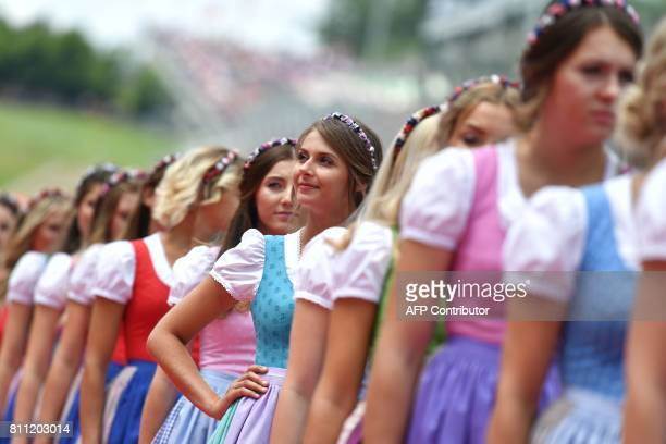 Official hostesses smile prior to the Formula One Austria Grand Prix at the Red Bull Ring in Spielberg on July 9 2017 / AFP PHOTO / Andrej ISAKOVIC