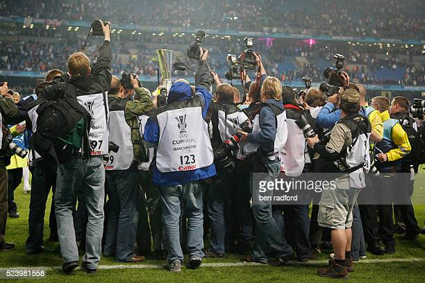 Official photographers take pictures of the FC Zenit St Petersburg players as they celebrate victory with the trophy after the UEFA Cup Final between...
