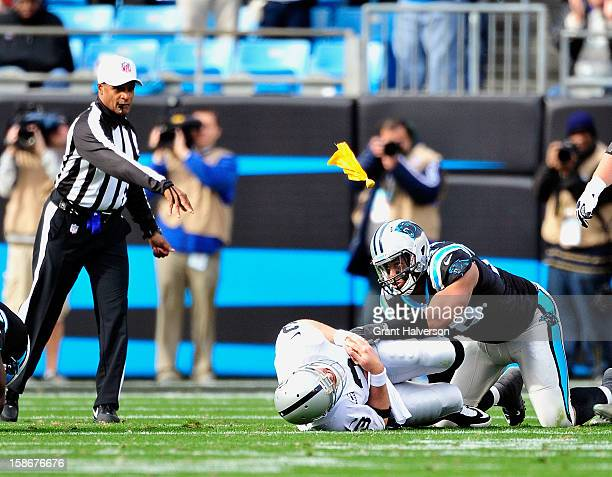 Official, referee Jerome Boger, throws a flag for roughing the passer as Greg Hardy of the Carolina Panthers tackles Carson Palmer of the Oakland...