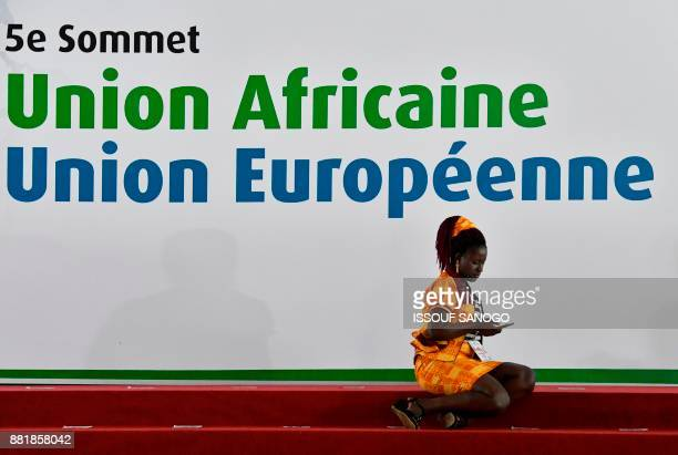 A official sits in front of the African Union European Union summit banner in Abidjan on November 29 2017 / AFP PHOTO / ISSOUF SANOGO