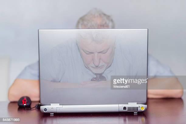 Official sleeping behind laptop