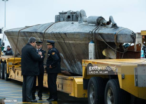 Official stand near a submarine used to transport drugs illegally in Aldan northwestern Spain on November 27 2019 Police in Spain have seized a...
