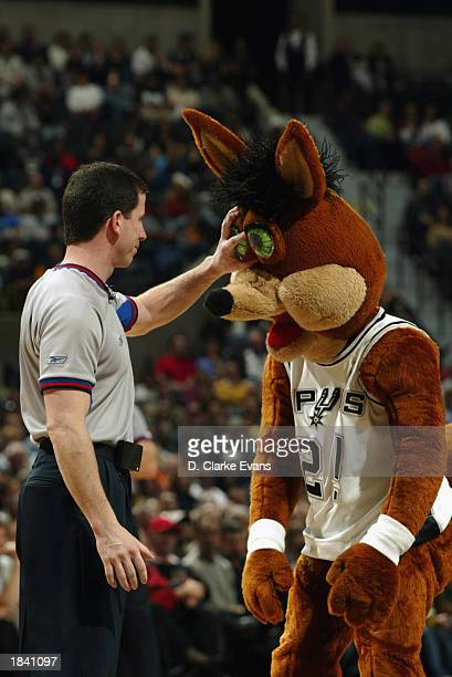 Official Tim Donaghy attaches the Velcro eyes of the Coyote, the Spurs mascot back to his face after they fell off during the NBA game between the...