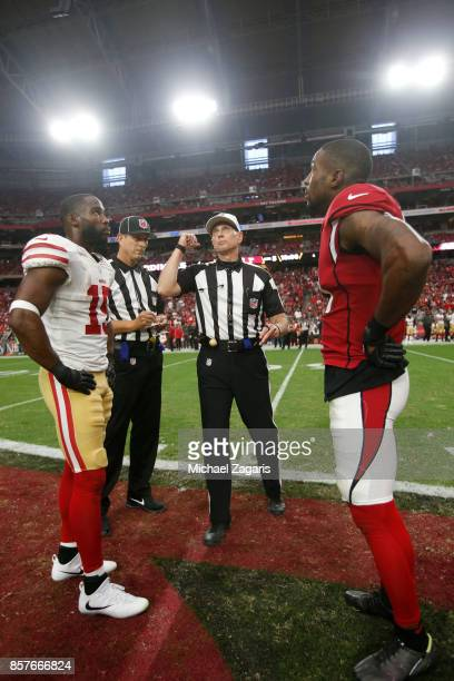Official Tony Corrente tosses the coin prior to the start of overtime between the San Francisco 49ers and the Arizona Cardinals at the University of...