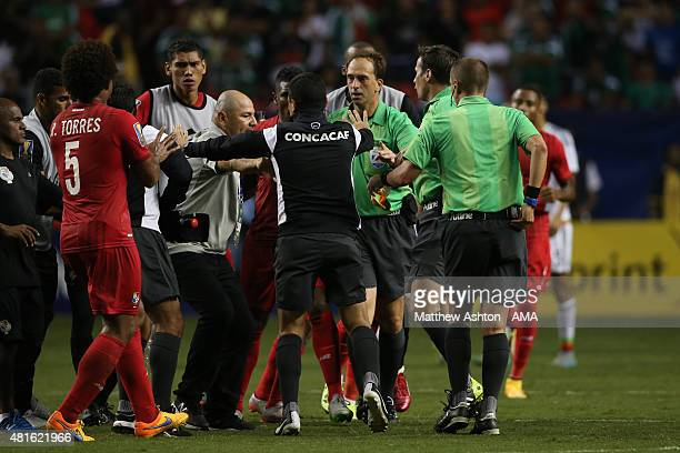 CONCACAF official tries to protect Referee Mark Geiger at the end of the game from being confronted by Panama players after the Gold Cup Semi Final...