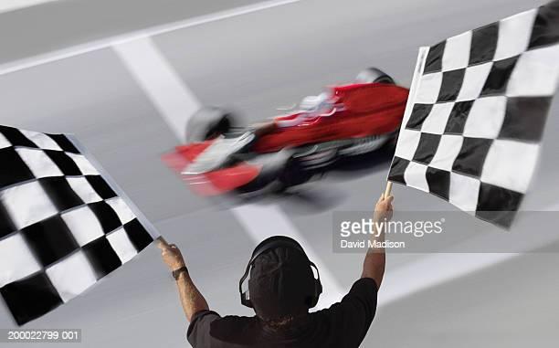 official waving checkered flags at car crossing finish line - carrera de coches fotografías e imágenes de stock