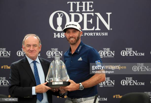 Official World Golf Ranking Chairman Peter Dawson presents Dustin Johnson of the United States with the OWGR McCormack Award during a practice round...