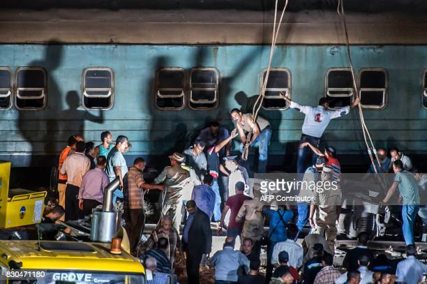 Officials and emergency personnel remove the wreckage of a collision between two trains on August 11 2017 near Khorshid station in Alexandria At...