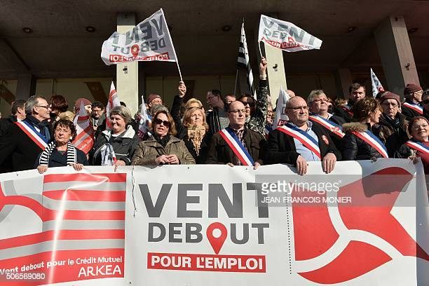 Officials and employees hold a banner reading 'headwind for employment' on January 24 in front of the townhall of Brest northwestern France during a...