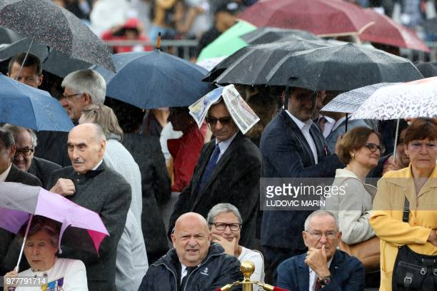 Officials and families of veterans shelter from a downpour of rain as they take part in a ceremony, commemorating General Charles De Gaulle's June...