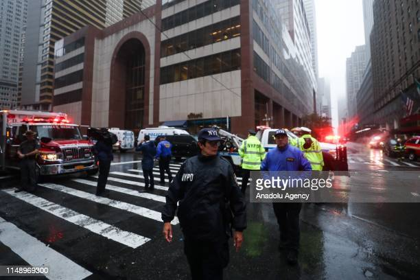 Officials and firefighters work around the crash site after a helicopter was forced into an emergency landing and crashed on top of a building in...