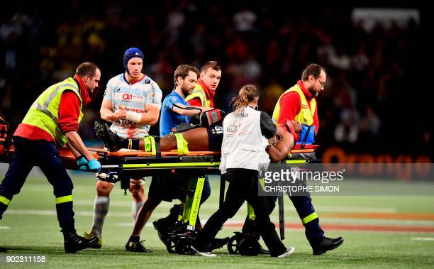 TOPSHOT Officials and medical personnel use a trolley to move the injured Clermont winger Samuel Ezeala from the pitch during the France Top 14 rugby...