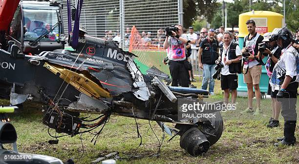 Officials and photographers look on as they remove the McLaren Honda car wreckage of Spanish driver Fernando Alonso after he crashed spectacularly...