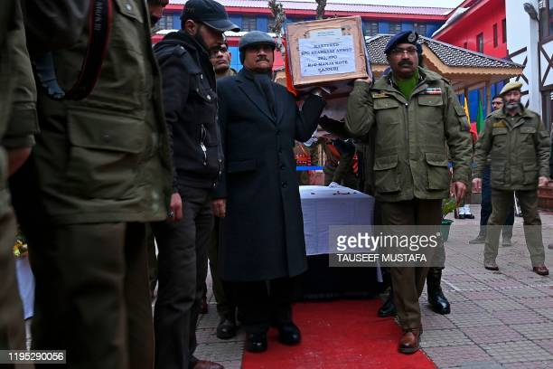 Officials and police officers carry the coffin of a slain colleague following a gun battle between suspected militants and government forces in Khrew...