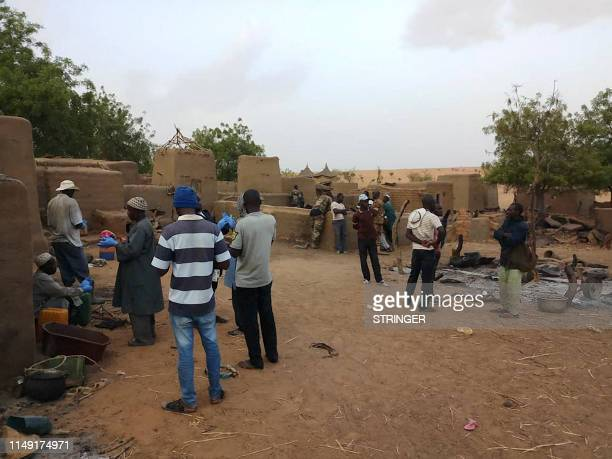 Officials and residents stand on June 11 2019 in the Dogon village of SobaneKou near Sangha after an attack that killed over 100 ethnic Dogon on June...