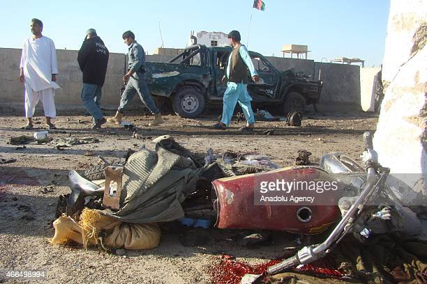 Officials are seen at the crime scene after a suicide attack at police checkpoint in Southern City Helmand of Afghanistan on March 16 2015 Attack...
