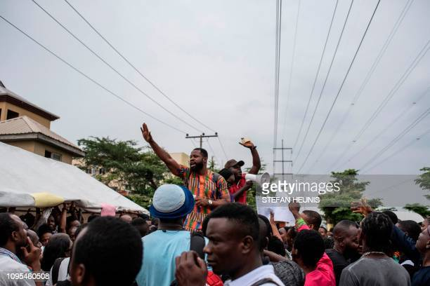 Officials at one of the Permanent Voter Cards collection points gesture to the crowd to remain patient in Lagos on February 8 2019 Would be voters...