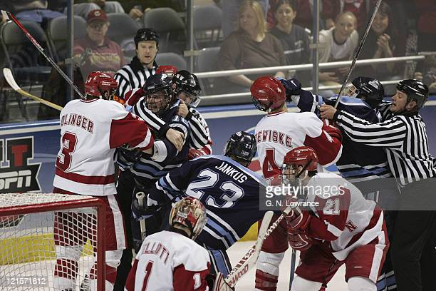 Officials attempt to break up a fight late in the Wisconsin versus Maine semi-final game of the NCAA frozen four at the Bradley Center in Milwaukee,...