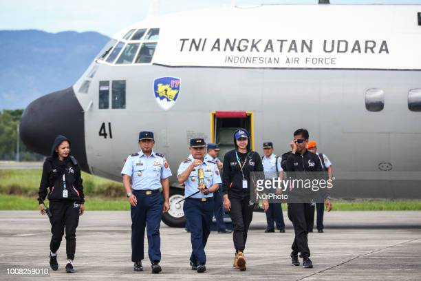 Officials carries the Asian Games torch from a military plane arriving from Banjarmasin ahead of the 18th Asian Games taking place in Jakarta and...