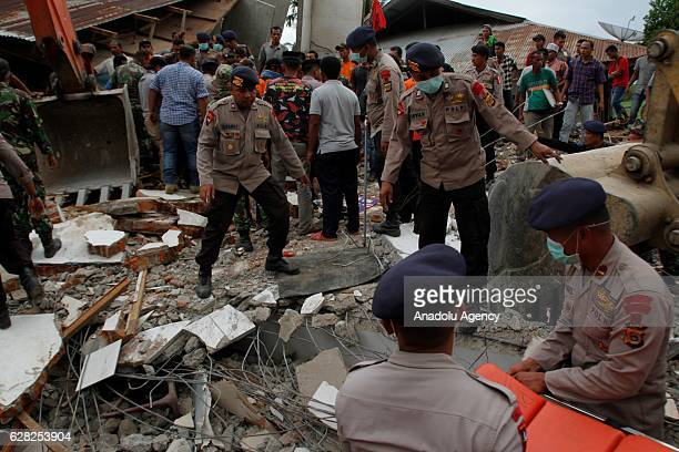 Officials carry out search and rescue works on the debris of a collapsed building after a strong earthquake shook the north of Indonesia's Sumatra...