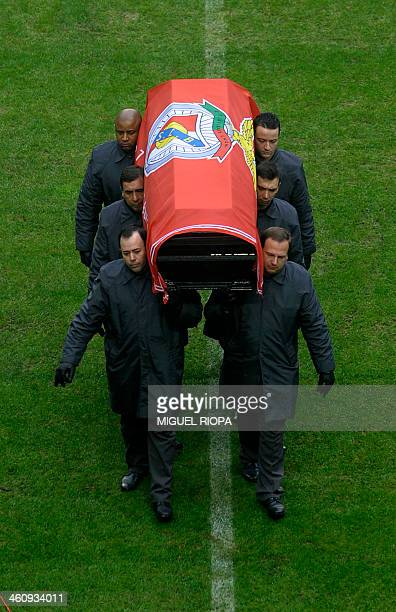 Officials carry the coffin of Benfica football legend Eusebio da Silva Ferreira on the pitch of the Luz stadium in Lisbon on January 6 2014 Tens of...