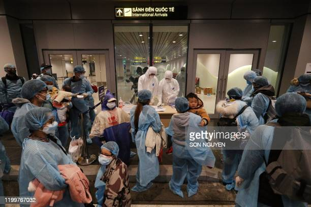 TOPSHOT Officials check details of Vietnamese citizens repatriated from Wuhan where the SARSlike novel coronavirus originated upon their arrival at...