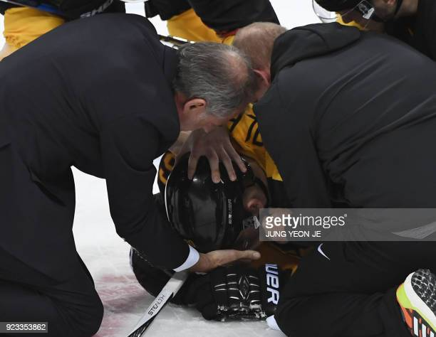 TOPSHOT Officials check on David Wolf as he lies on the ice in the men's semifinal ice hockey match between Canada and Germany during the Pyeongchang...