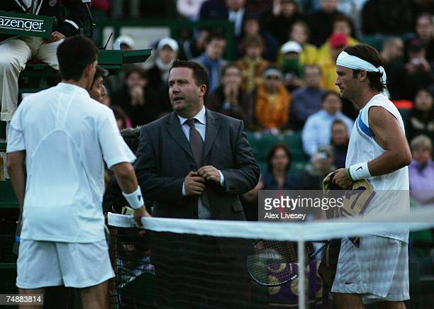 Officials discuss the possible end of play due to bad light as Tim Henman of Great Britain and Carlos Moya of Spain during his Men's Singles first...