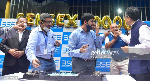 Officials, employees and traders celebrate by releasing balloons and cutting a cake as Bombay Stock Exchange benchmark Sensex crosses 60,000 level...