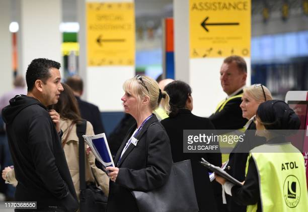 Officials from Britain's Civil Aviation Authority hold information for Thomas Cook passengers at Manchester Airport in Manchester northern England on...