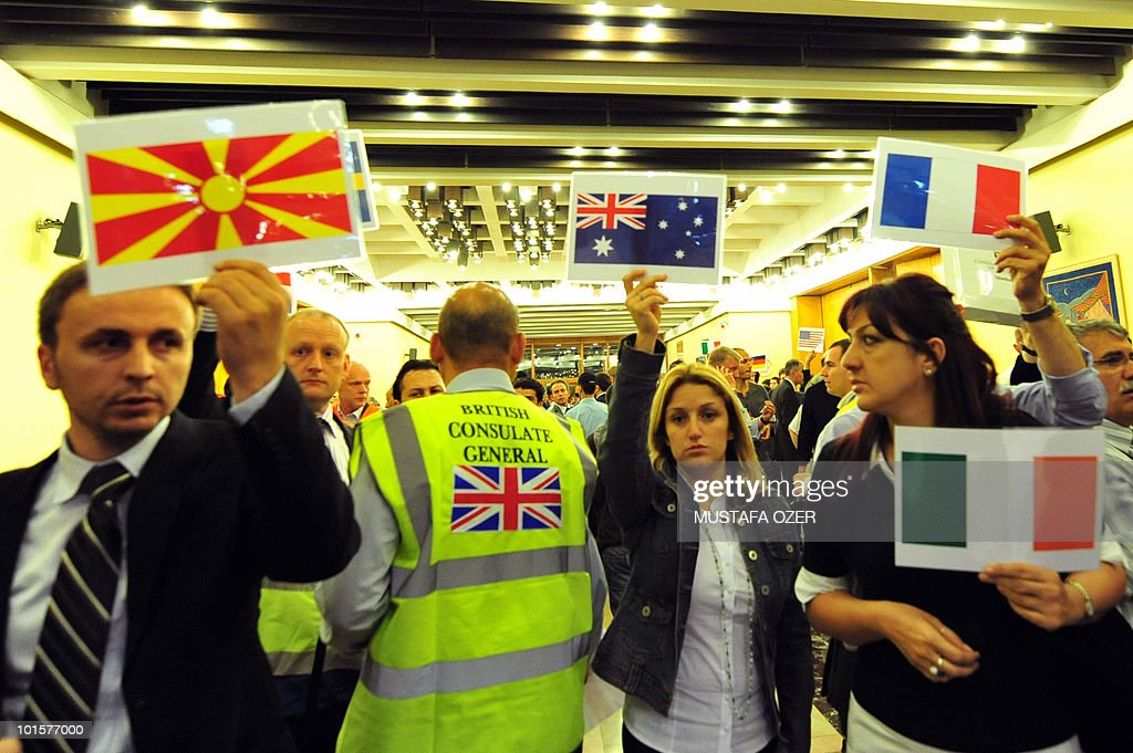 Officials from European consulates hold up placards with national flag as they wait for compatriots expelled from Israel to arrive on June 3, 2010 at Istanbul airport. Turkey began flying wounded activists from Israel Wednesday in a large-scale repatriation operation after an Israeli raid on Gaza-bound aid ships that claimed nine lives and sparked global outrage.